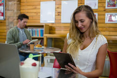Jeune femme à l'aide du comprimé en café image libre de droits