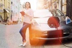 Jeune femme à l'aide du comprimé tout en chargeant la voiture Image libre de droits