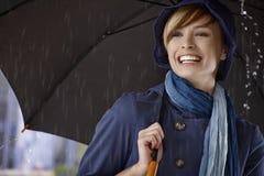 Jeune femme à l'aide du parapluie sous la pluie Images stock