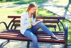 Jeune femme à l'aide du PC de comprimé sur le banc dans le parc de ville Image libre de droits