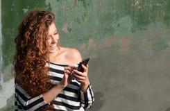 Jeune femme à l'aide du smartphone Photographie stock libre de droits