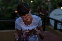 Jeune femme à l'aide du smartphone dehors à la nuit Île de Bali Photos stock