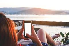 Jeune femme à l'aide du smartphone noir avec le whi de bureau vide d'écran Photographie stock libre de droits