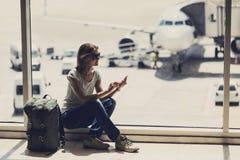 Jeune femme à l'aide du smartphone pendant l'aéroport, le voyage, les vacances et le concept actif de mode de vie image stock