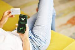 Jeune femme à l'aide du smartphone pour le paiement en ligne à la maison, se reposant sur le divan photo libre de droits