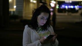 Jeune femme à l'aide du téléphone dehors, sms d'impression la nuit De belles lumières de la ville de nuit peuvent être vues à l'a banque de vidéos
