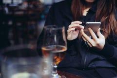 Jeune femme à l'aide du téléphone intelligent à la barre Images libres de droits