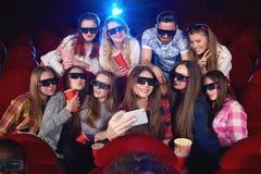 Jeune femme à l'aide du téléphone intelligent au cinéma Photos stock
