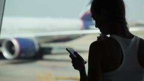 Jeune femme à l'aide du téléphone intelligent et mangeant des casse-croûte à l'aéroport banque de vidéos
