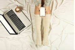 Jeune femme à l'aide du téléphone intelligent sur son lit Femme travaillant à l'ordinateur portable et au café de cappuccino de b Photo stock