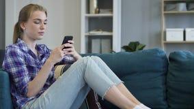 Jeune femme à l'aide du téléphone intelligent tout en détendant sur le divan images libres de droits