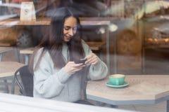 Jeune femme à l'aide du téléphone portable dans le vitrail de throuth de café photos stock