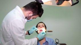 Jeune femme à l'examen dentaire banque de vidéos