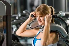 Jeune femme à l'exercice de centre de forme physique abdominal Images stock