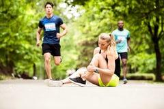 Jeune femme à la concurrence avec la cheville foulée image stock