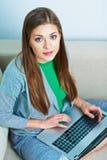 Jeune femme à la maison avec l'ordinateur portatif Photos stock