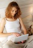 Jeune femme à la maison dans le lit utilisant l'ordinateur portable Photographie stock libre de droits