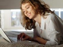 Jeune femme à la maison dans le lit utilisant l'ordinateur portable Image stock