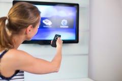 Jeune femme à la maison regardant la TV Photographie stock
