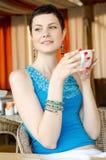 Jeune femme à la maison sirotant le thé d'une cuvette Images libres de droits