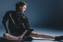 Jeune femme à la mode élégante s'asseyant sur le plancher au studio Image libre de droits