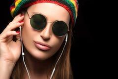 Jeune femme à la mode appréciant la musique par l'écouteur Photos stock
