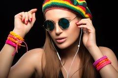 Jeune femme à la mode appréciant la musique par l'écouteur Images stock