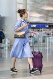Jeune femme à la mode avec la valise à l'aéroport international capital de Pékin Photographie stock