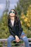 Jeune femme à la mode dans des vêtements de style de roche, veste en cuir noire, blues-jean, collants dans une grille sous les je Images stock