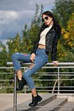 Jeune femme à la mode dans des vêtements de style de roche, veste en cuir noire, blues-jean, collants dans une grille sous les je Images libres de droits