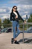 Jeune femme à la mode dans des vêtements de style de roche, veste en cuir noire, blues-jean, collants dans une grille sous les je Photos libres de droits