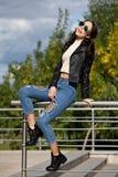 Jeune femme à la mode dans des vêtements de style de roche, veste en cuir noire, blues-jean, collants dans une grille sous les je Image stock