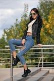 Jeune femme à la mode dans des vêtements de style de roche, veste en cuir noire, blues-jean, collants dans une grille sous les je Photos stock