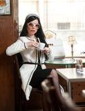 Jeune femme à la mode en café potable d'équipement noir et blanc dans le restaurant Belle brune dans le paysage élégant Photographie stock libre de droits