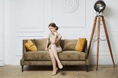 Jeune femme à la mode et belle de modèle de brune, dans la robe beige, posant sur le sofa au fond de luxe Photo stock