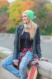 Jeune femme à la mode occasionnelle avec son panneau de patin Photographie stock