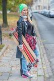 Jeune femme à la mode portant un panneau de patin Photographie stock