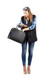 Jeune femme à la mode recherchant quelque chose dans son sac à main Photos stock