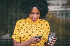 Jeune femme à la peau foncée habillée dans des vêtements sport tenant la tasse de la boisson chaude images stock