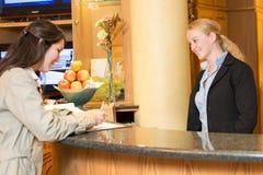Jeune femme à la réception d'hôtel photographie stock libre de droits