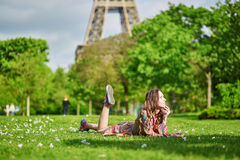 Jeune femme à Paris se trouvant sur l'herbe près de Tour Eiffel un beau jour de ressort ou d'été Photos stock