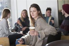 Jeune femme à un café avec ses amis Photo libre de droits