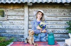 Jeune femme à un chapeau d'été de paille et à son arrière-plan rural de petit chien Image libre de droits