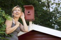 Jeune femme écoutant la maison d'oiseau Photo stock
