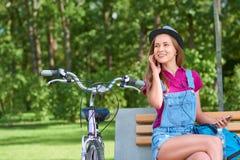 Jeune femme écoutant la musique à son téléphone intelligent se reposant au image stock