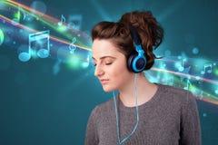 Jeune femme écoutant la musique avec des écouteurs Photo stock