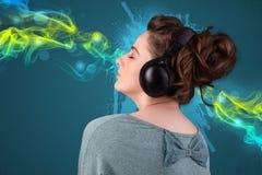 Jeune femme écoutant la musique avec des écouteurs Photographie stock