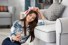 Jeune femme écoutant la musique par des écouteurs Photographie stock libre de droits