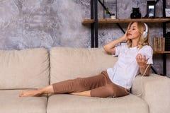 Jeune femme écoutant la musique tout en détendant sur le sofa à la maison image stock