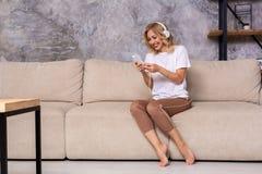 Jeune femme écoutant la musique tout en détendant sur le sofa à la maison photo stock
